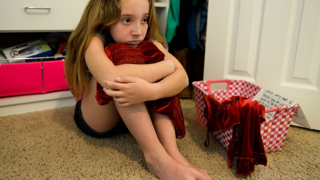 Amanda Orza, 10, with a sleeveless red dress that her mom bought for her and she wore the night her mom and eight other family members were murdered on Christmas Eve 2008.