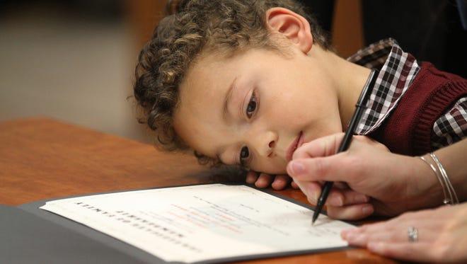Jisaiah Conroy, 4, of Greece watches as his parents take turns signing his adoption paper.