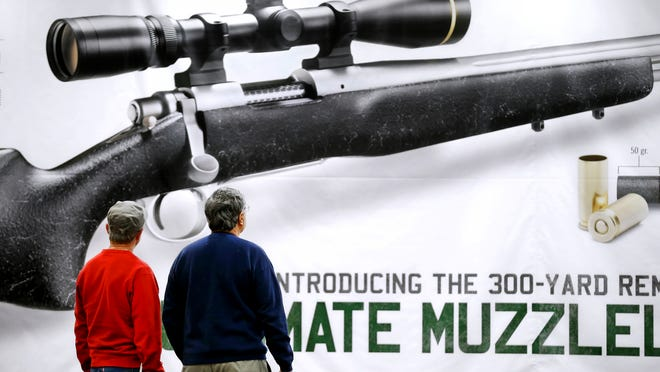 John Lumm and Roger Genereaux, both of Lancaster, Ohio, admire a giant ad for the new Remington Muzzeloader that was on the wall at the Convention Center on Thursday. The NRA convention officially kicks off Friday morning. It's expected to draw 70,000 people Downtown, pumping $55 million into the local economy.
