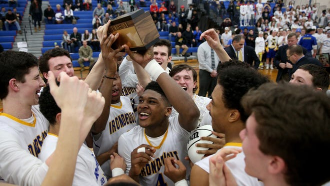 Irondequoit's Gerald Drumgoole (4) celebrates with teammates after the Eagles beat Greece Athena 61-44 to win the Class A1 title on March 4, 2017.