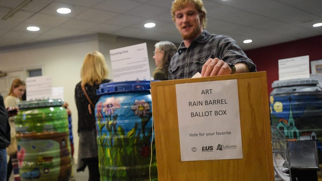 Luke Provost casting ballot for his favorite Rain barrel designed and painted by middle schools that are being unveiled for public voting at Chase Towers at ArtWalk.