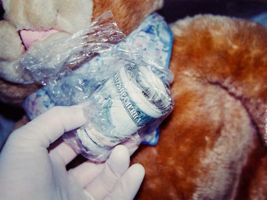 Money found hidden in a teddy bear is shown as a part