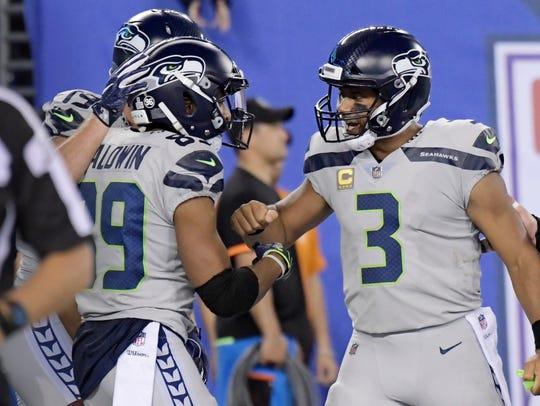 Seattle Seahawks quarterback Russell Wilson, right,