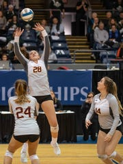 Farmington Hills Mercy's Julia Bishop (28) sets the ball for Mallory Conrad (24) and Maddy Benoit (14) during MHSAA Volleyball semifinals at Kellogg Arena in Battle Creek on Friday.