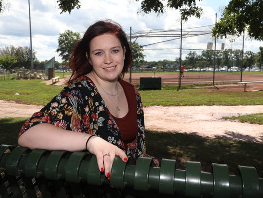 Skyler Spina sits on a bench dedicated in her father,