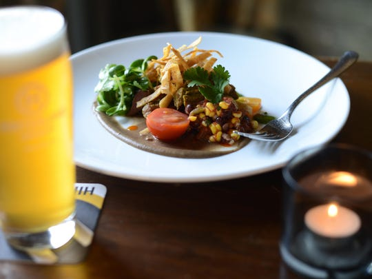 Food like this pork verde with a black bean puree, corn salsa, sunflower sprouts and corn crisps, has been part of Hinterland's success during its first 20 years.