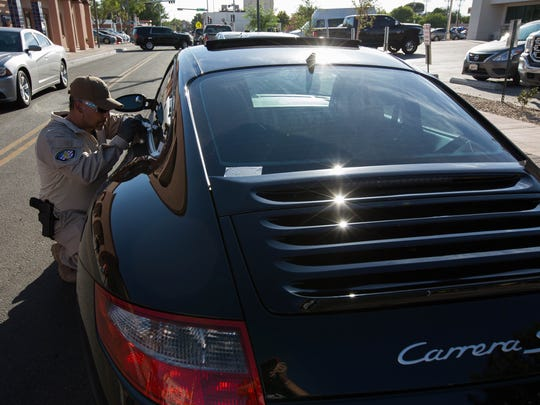 Special Agent Johnny Cappelli with the Office of the Superintendent of Insurance, uses acid to etch the VIN number onto a Porche Carrera S, Tuesday August 7, 2018 during National Night Out on Main Street.