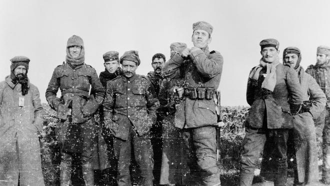 In this image provided by the Imperial War Museum, World War I German and British soldiers stand together on the battlefield near Ploegsteert, Belgium in Dec. 1914. A century ago on Christmas Day, German and British enemies left their World War I trenches and headed into no man's land in a few scattered locations on the Western Front for an unofficial truce among soldiers.
