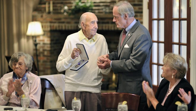 Sen.Tom Carper presents a Purple Heart to WW II and Korean War veteran William Brady for wounds he received from enemy fire more than 60 years ago.
