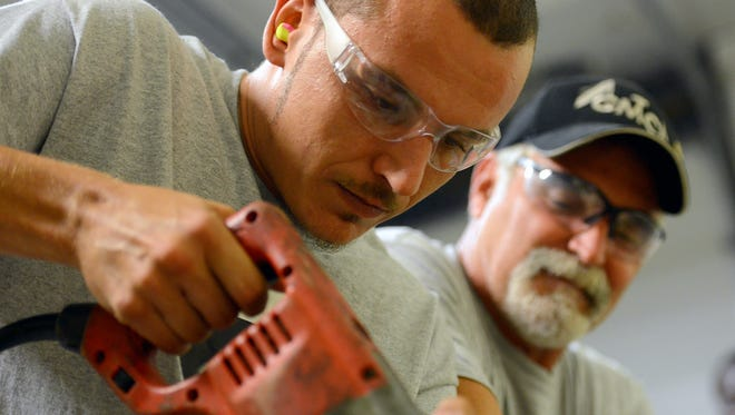 James Ormsbee practices making straight, 90-degree cuts with a  sawzall as instructor Barry Bartynski watches during a class of the BOP Program Aug. 30, 2016 in Lansing. The program - which stands for Building Opportunities for People - is a partnership between Consolidated Electric, the Greater Michigan Construction Academy and the Homeless Angels.