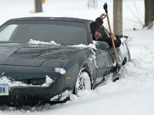 A woman, who would  not give her name, tries to clear snow from her door so she can get out, after getting stuck in a snowbank on Lyon Street on the east side of Des Moines in February 2008.