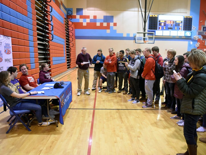 Athletes sign their letters of intent during a signing