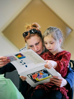 Jaidyn Hemze, 5, shows her mom Erin Renczykowski the Picture Writing book she created during an after-school activity program Monday at Bel Clare Estates.