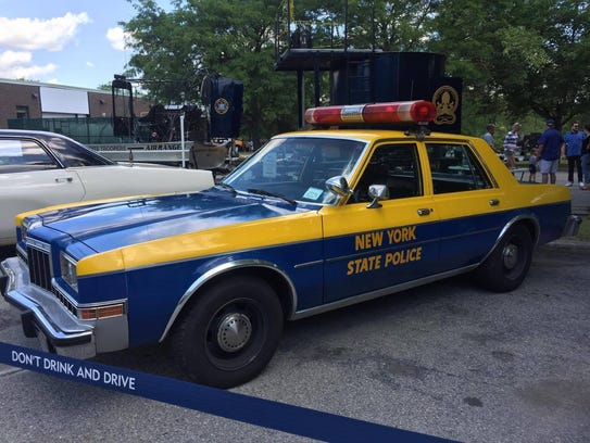 A state police vehicle from the 1970's sits outside