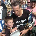 Novi resident Ashton Molnar, 10 is thrilled to get his skateboard signed by Tony Hawk.