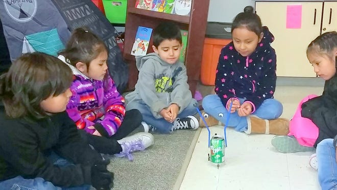 Students in Rose Helmke's 1st-grade class in Mescalero watch a robot made by Abrina Chee, in dark jacket. Abrina is the youngest of four elementary students in the high school STEM program, which emphasizes science, technology, engineering and mathematics.