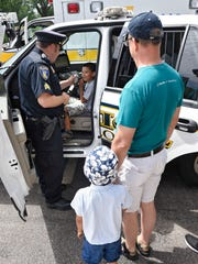 Children get the chance to sit in a police vehicle during Saturday's Celebration of Fatherhood Event at Lake George in St. Cloud.