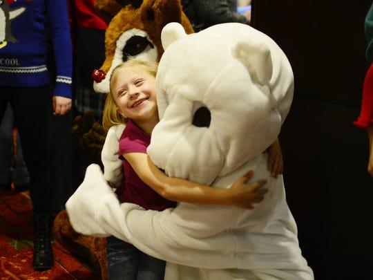 Brianna Partlow, 6, of Burlington hugs a person dressed