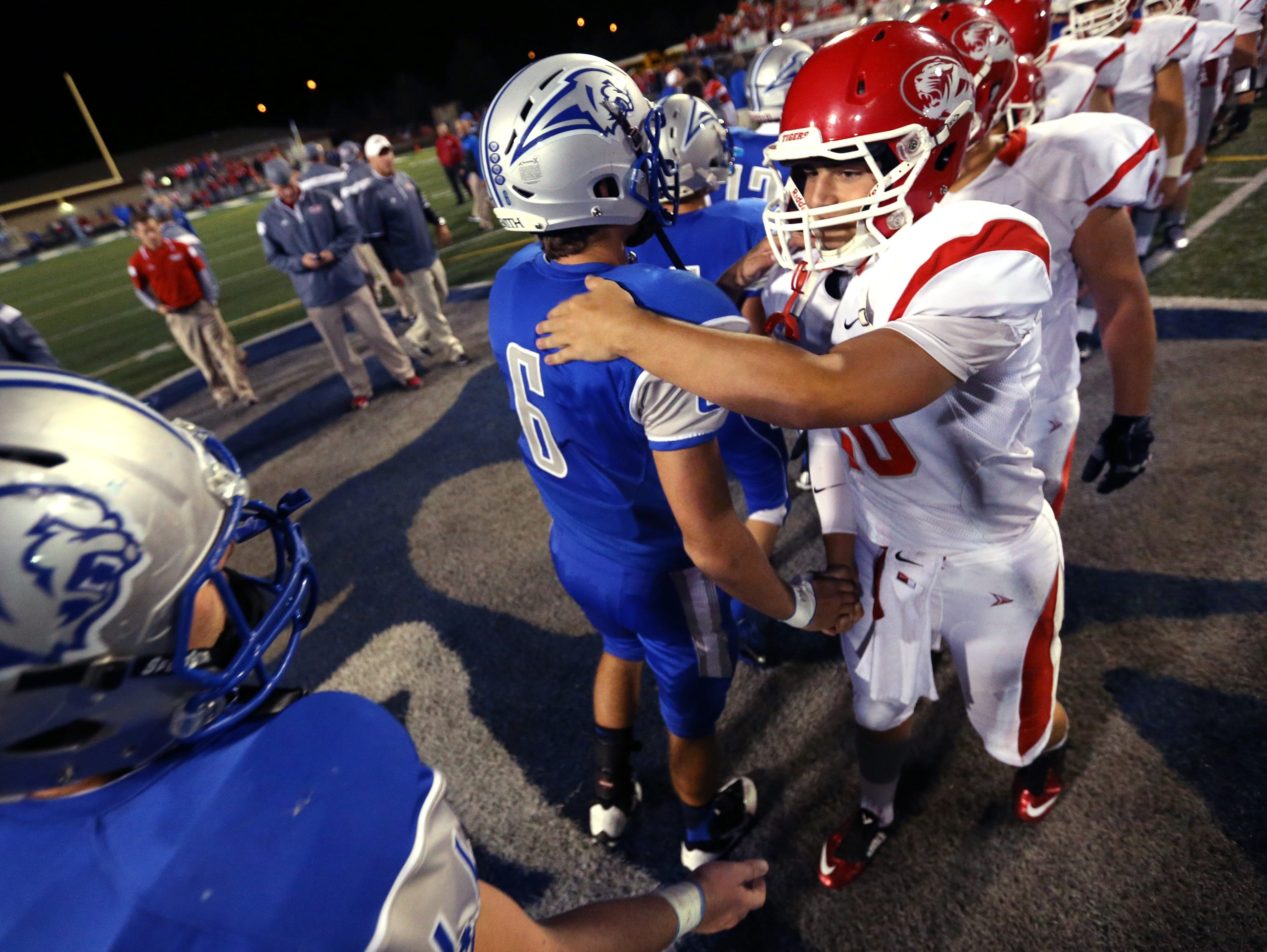 Fishers Tigers quarterback Zach Eaton shakes hands with Hamilton Southeastern's grant Skelton after the Tigers' 41-10 win over the Royals at HSE on Friday, September 12, 2014.