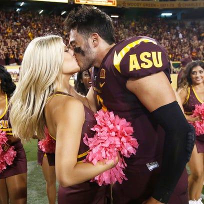 Arizona State quarterback Mike Bercovici kisses a cheerleader