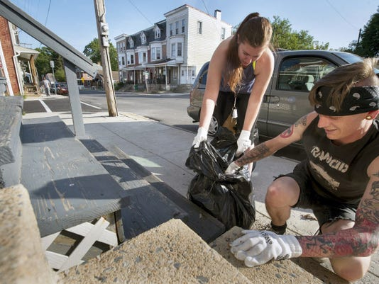 """Catie Myers and Steve Klinedinst clean trash out between two steps during a garbage cleanup along South Belvidere Avenue in York. Klinedinst and his friend, Dustin Hildebrand, launched Punks for Positivity, a nonprofit group that organizes cleanups in the city. In the last couple months, the """"punks"""" have picked up drug paraphernalia, blunt wrappers, discarded bones from chicken wings, condoms and a full pack of cigarettes."""