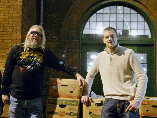 Dion Boyer of North York and Michael Fourhman of Springfield Township stand for a portrait with a trailer of 50-pound boxes of food on Friday, April 3, 2015, outside Central Market on Cherry Lane in York. Every Friday since last November, Michael Fourhman and Dion Boyer have given away 50-pound boxes of free food donated by area stores and church partnerships. Fourhman, who owns Fourhman's Natural Foods in York Township and recently opened a booth at Central Market, is working to start a 501(c)(3) organization to facilitate and expand the weekly food giveaways. He estimates that, as of April 3, he and Boyer have distributed about 7.5 tons of free food since the beginning of January 2015. Chris Dunn — Daily Record/Sunday News
