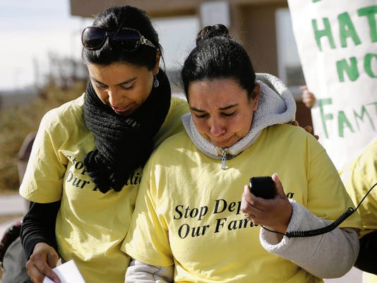 Elsa Lopez, left, of Somos Un Pueblo Unido comforts plaintiff Susana Palacios-Valencia as she reads a statement Wednesday outside the San Juan County Adult Detention Center in Farmington.