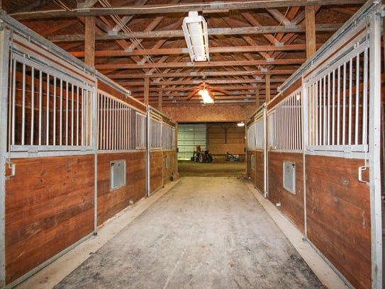 The property includes a barn with indoor riding arena