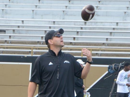 Western Michigan head football coach Tim Lester tosses