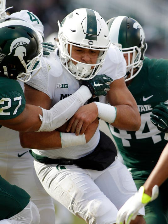 Michigan State running back Connor Heyward, center, rushes for a touchdown against safety Khari Willis, left, and Grayson Miller during the first half of an NCAA college football scrimmage, Saturday, April 7, 2018, in East Lansing, Mich. (AP Photo/Al Goldis)