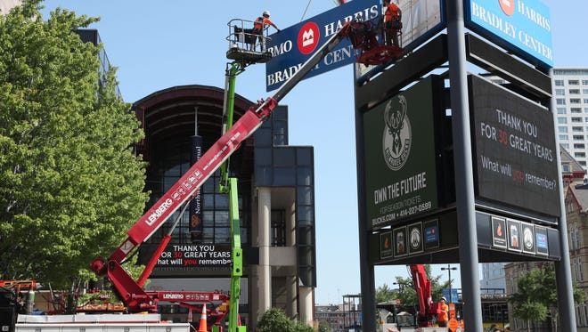 July 25, 2018 A crew from Lemberg Sign and Lighting, takes down signage from in front of the BMO Harris Bradley Center.  Chris Leu (center left) and Chad Setterbo (center right) guide the sign as its lowered to the ground.