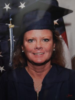 A photo from Theresa Supino's graduation from Des Moines Area Community College in December 2008 is shown hanging on the wall of her home in Altoona on Tuesday, March 4, 2014. Theresa was arrested on Monday, March 3 on two counts of first-degree murder in the deaths of Steven Fisher and Melisa Gregory.