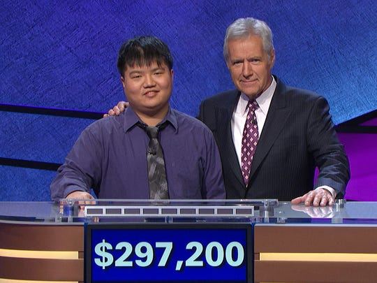 "Host Alex Trebek with contestant Arthur Chu in front of a total of his winnings at a taping of ""Jeopardy,"" in Culver City, Calif. Chu, who won big money while taking heat for his renegade style, has been defeated."