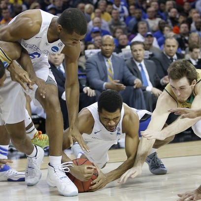 Kentucky Wildcats guard Andrew Harrison (5), center, dives for a loose ball during the NCAA Tournament college basketball Round of 8 game against Notre Dame, Saturday, March 28, 2015, at Quicken Loans Arena in Cleveland.