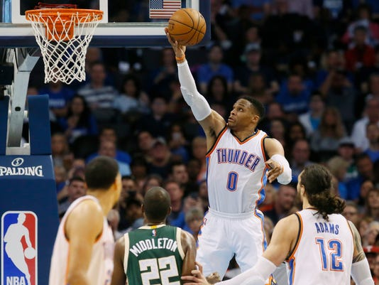 Oklahoma City Thunder guard Russell Westbrook (0) shoots in front of Milwaukee Bucks guard Khris Middleton (22) and teammates Andre Roberson, left, and Steven Adams (12) in the second quarter of an NBA basketball game in Oklahoma City, Tuesday, April 4, 2017. (AP Photo/Sue Ogrocki)