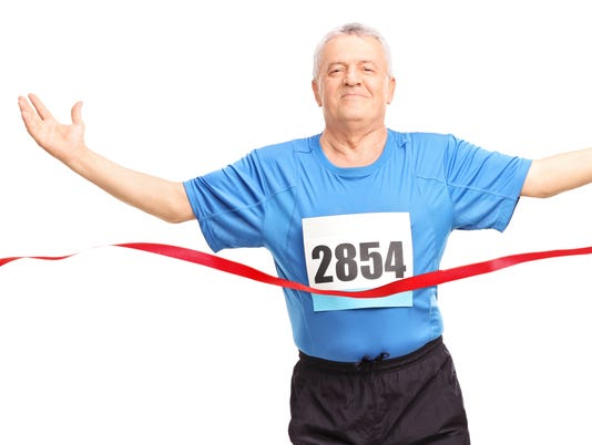 Mature runner finishing a race and celebrating his victory