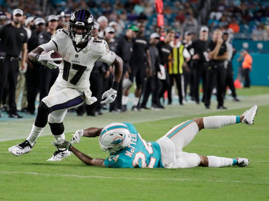 Miami Dolphins cornerback Torry McTyer (24) attempts to tackle Baltimore Ravens wide receiver Jordan Lasley (17) during the second half of a preseason NFL game, Saturday, Aug. 25, 2018, in Miami Gardens, Fla. (AP Photo/Lynne Sladky)