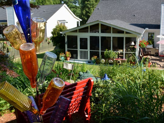 From the upper shade garden, a colorful bottle tree frames the view of the Marckini's home.
