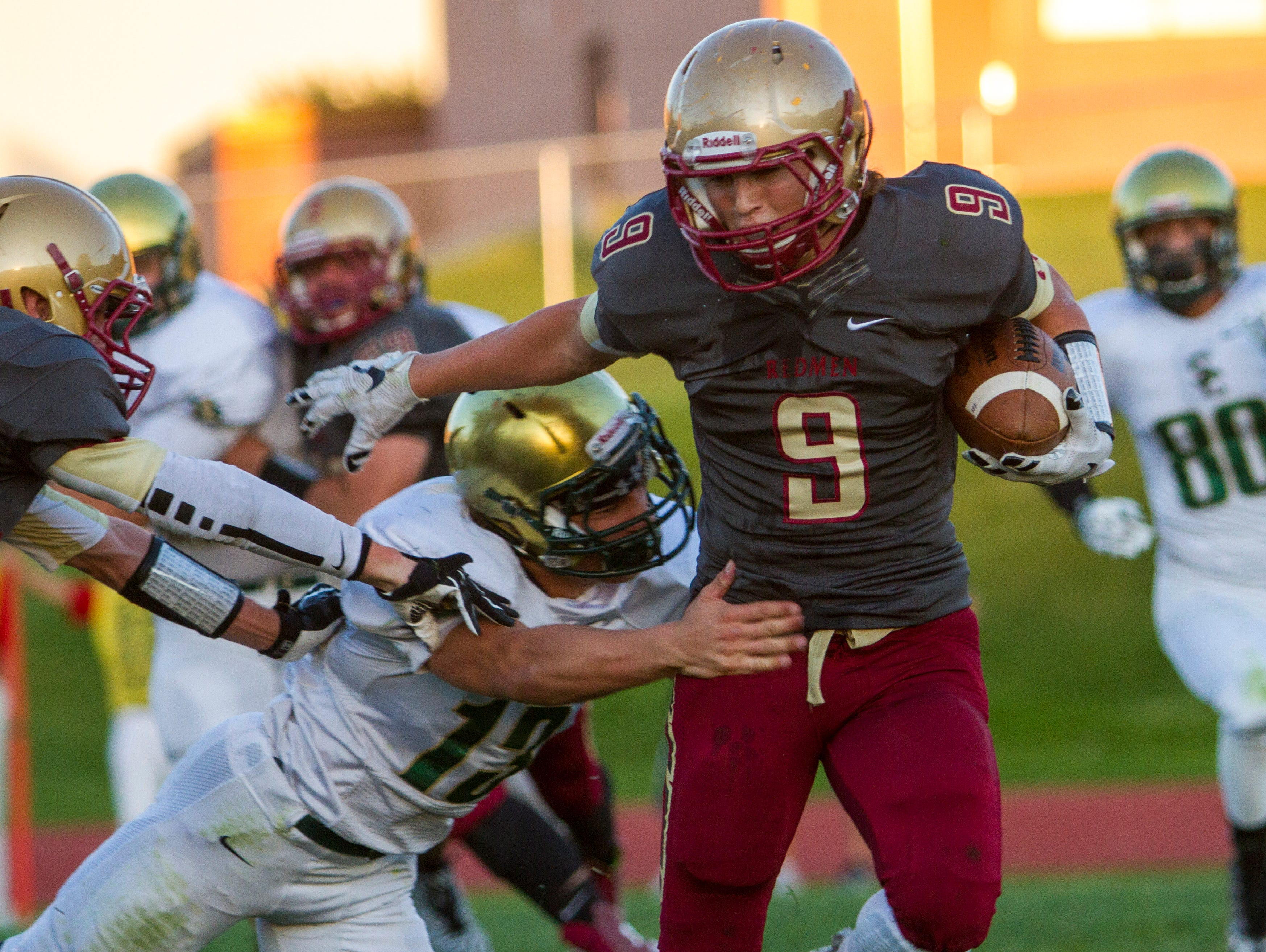 Cedar's Drake Lewis (#9) breaks a tackle on his way to a touchdown against Snow Canyon, Friday, Sept. 25, 2015.
