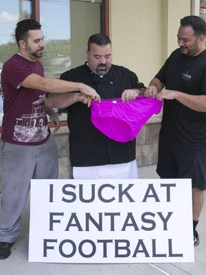 Angelo Boemio (center), of Toms River, came in last in his fantasy football league. As punishment, he had to walk down Route 9 dressed only in pink panties and carrying this sign. A video of his walk of shame went viral. Boemio is with Andy Esposito (left) and Mike Durazzo, two other players in his fantasy league