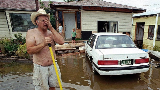 In this July 29, 1997 photo, Gil Boyer rubs his head while wading in flood waters outside his home in northwest Fort Collins, Colo. Forecasters expect Bruce Lee, the moniker some forecasters are using for the current El Nino, to be among the most powerful El Ninos in the last half-century.