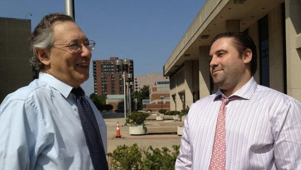 Adam Heller, right, speaks with his attorney after making a court appearance July 22, 2014, regarding his dismissal from the Bedford school district.