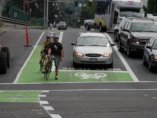 Portland, Ore. has installed several bike boxes, like this one, since 2008 to prevent bike and car crashes between drivers turning right and bicyclists going straight. At red lights, bicyclists become more visible by being in front of motorists. The green bike lane through the intersection reminds motorists and bicyclists to watch for each other.