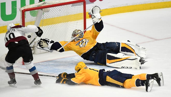 The game-winning goal by Colorado Avalanche right wing Sven Andrighetto (10) gets by Nashville Predators goaltender Pekka Rinne (35) during the third period in game 5 of the first round NHL Stanley Cup Playoffs at the Bridgestone Arena Friday, April 20, 2018, in Nashville, Tenn.
