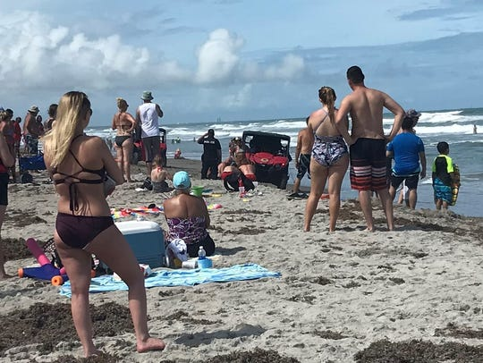 Lifeguards apply CPR to a woman who was pulled from