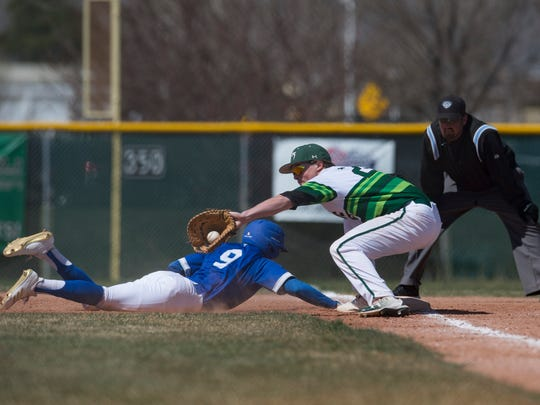 Fossil Ridge High School first baseman Everett Barnes catches the ball as Poudre baserunner Sergio Tarango dives safely back to first base during a game April 14, 2018, between the cross-town rivals. The two teams will meet again at 4 p.m. Wednesday at Fossil Ridge.
