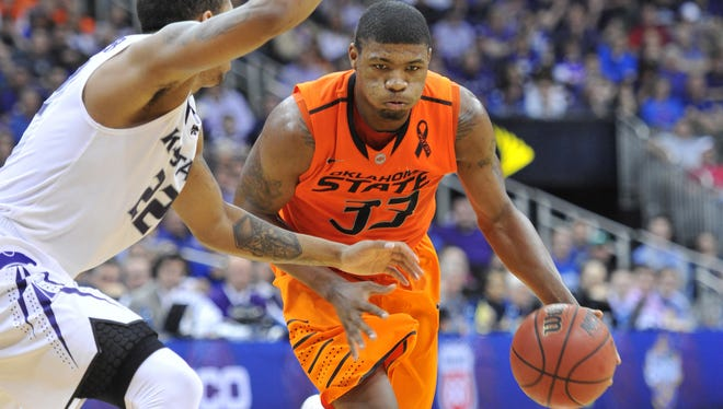 Oklahoma State guard Marcus Smart (33) drives against Kansas State guard Rodney McGruder (22) in the quarterfinals of the Big 12 tournament March 15 at the Sprint Center in Kansas City. Smart is the 2012-13 and 2013-14 preseason Big 12 Player of the Year.
