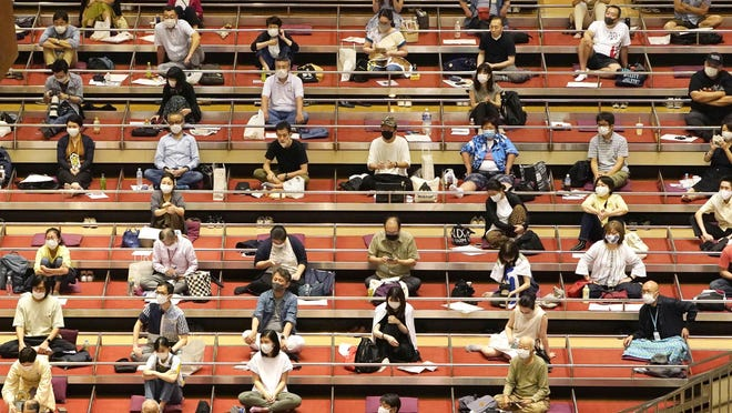 Sumo spectators wearing face mask practice social distance in their seats during the outbreak of the new coronavirus as they watch the first day of the sumo tournament in Tokyo, Sunday, July 19, 2020.