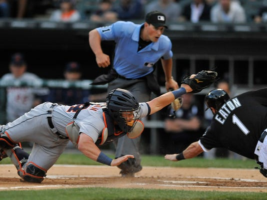 Detroit Tigers catcher James McCann left, misses the tag as Chicago White Sox's Adam Eaton (1) slides safely into home plate on a Melky Cabrera sacrifice fly ball during the first inning of a baseball game Tuesday, June 14, 2016, in Chicago. (AP Photo/Paul Beaty)