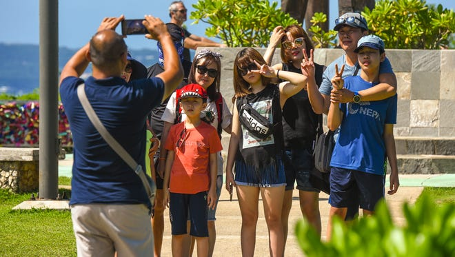 Tourists pose for a group photo during their visit to Puntan Dos Amantes, or Two Lovers' Point, on Friday, Oct. 20, 2017.